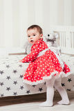 A one-year-old girl in a red dress takes her first steps holding onto the bed in the room.  Royalty Free Stock Image