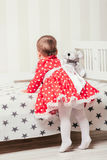 A one-year-old girl in a red dress takes her first steps holding onto the bed in the room.  Royalty Free Stock Images