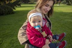 One year old girl sits by her mother in her arms and is happy looking at the camera. royalty free stock photo