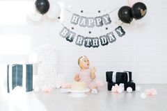 A one-year-old girl sits near a cake, celebrates her first birthday in a photo zone in white-pink-black tones
