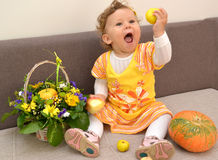 The one-year-old girl sits on a sofa, holds apples in hand and loudly laughs Royalty Free Stock Photo