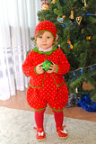 The one-year-old girl in a suit of strawberry stands near a New Year tree Royalty Free Stock Photo