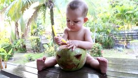 A one year old infant baby sits on a wooden table against the background of palm trees and drinks coconut milk from a straw. A fac. E is carved on a coconut like stock video footage