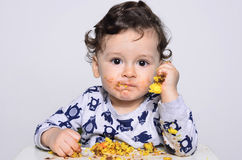 One year old kid eating a slice of birthday smash cake by himself getting dirty. Royalty Free Stock Photo