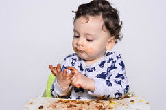 One year old kid eating a slice of birthday smash cake by himself getting dirty. Stock Photo