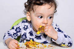 One year old kid eating a slice of birthday smash cake by himself getting dirty. Stock Photos
