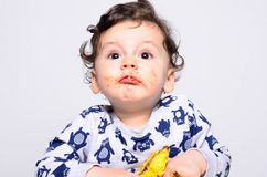 One year old kid eating a slice of birthday smash cake by himself. Stock Photos