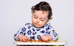 One year old kid eating a slice of birthday smash cake by himself. Royalty Free Stock Photo
