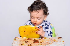 One year old kid eating a slice of birthday smash cake by himself. Stock Images