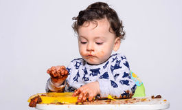 One year old kid eating a slice of birthday smash cake by himself. Stock Photo
