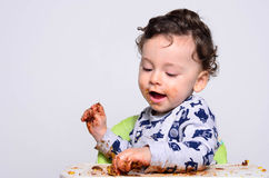 One year old kid eating a slice of birthday smash cake by himself. Royalty Free Stock Photos