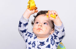 One year old kid eating a slice of birthday smash cake by himself. Royalty Free Stock Photography