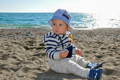 The one-year-old kid in a hat sitting on the beach Stock Photos
