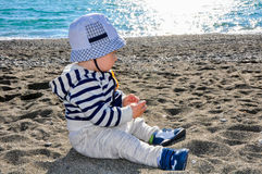 The one-year-old kid in a hat sitting on the beach Stock Photography