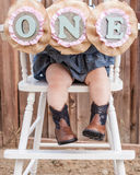 One year old little girls legs with cowgirl boots in a high chair. Little girl with cowboy boots on and a sign that says one Royalty Free Stock Photo