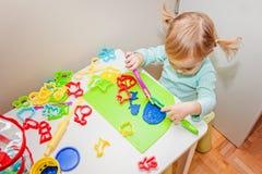 One year old toddler girl molding play dough. One year old toddler girl molding colorful play dough Stock Photos