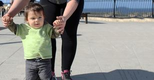 One year old todler learning how to walk with mother. On the suny day on playground stock images