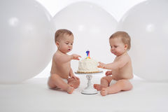 One Year Old Twin Boys with Birthday Cake. One year old twin brothers wearing diapers and eating their birthday cake. Shot in the studio with large, white stock photos