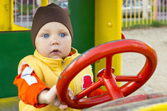 One year small boy at the car wheel. One year old boy at the wheel on kids playground in city in autumn season in Russia Stock Photo