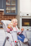 One year toddler girl sits on baby high chair with feeding bottle in her hand. Stock Photo