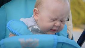 One years old baby boy sneezing in the pram. Close-up. Slow Motion.
