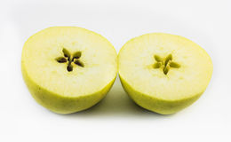 One yellow apple cut in half on a white background Royalty Free Stock Photography
