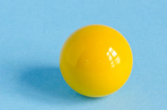One yellow billiards ball on azure background Stock Photo