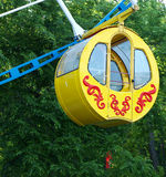 One yellow cubicle on Ferris wheel. On the background of green foliage stock image