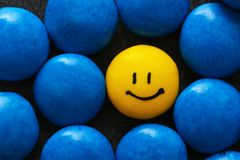 One yellow drop with painted happy face. Among blue ones. Difference and uniqueness concept royalty free stock photos