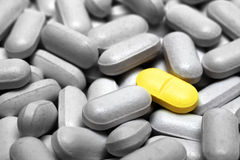 One yellow pill on gray pills Stock Photography