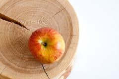 One yellow-red apple  on wooden stump and white copy space. Top Stock Photo