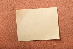 One yellow sticky post note closeup cork board background Royalty Free Stock Image