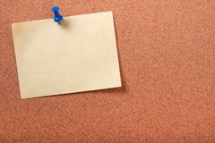 One yellow sticky post note pinned pushpin cork background Stock Images