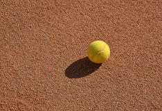 One yellow tennis ball on the clay tennis field. Photography stock photo