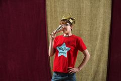 Actor dressed as king drinks. One young actor dressed as king wearing crown drinks from silver goblet Stock Photo