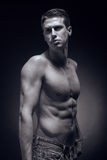 One young adult man, Caucasian, fitness model, muscular body, sh. Irtless, jeans, black background in studio, posing, looking sideways stock image