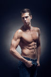 One young adult man, Caucasian, fitness model, muscular body, sh. Irtless, jeans, black background in studio, posing, looking sideways royalty free stock images