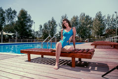 One young adult woman Caucasian model posing, sitting sunlounger. Outdoors, hot sunny day, swimming pool, trees, one piece swimsuit Royalty Free Stock Photography