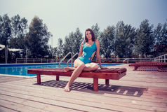 One young adult woman Caucasian model posing, sitting sunlounger. Outdoors, hot sunny day, swimming pool, trees, one piece swimsuit Stock Photos