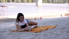 One young adult woman laying on blanket, reading a book. casual clothes, summer on beach. group of people out of focus, stock footage