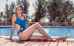 One young adult woman model, laying, swimming pool edge, water, Royalty Free Stock Image