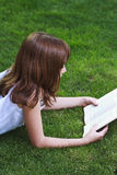 One.Young beautiful girl reading a book outdoor Royalty Free Stock Photography