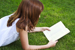 One.Young beautiful girl reading a book outdoor stock photo