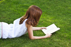 One.Young beautiful girl reading a book outdoor Stock Photos