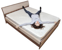 One young Caucasian girl is resting on bed innerspring mattress. Stock Photo
