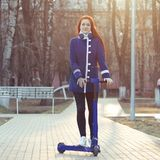 One young caucasian woman with red hair in a blue coat on a blue electric scooter in the park. Eco-friendly transport stock photo