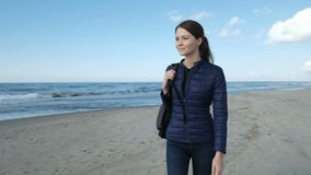 Girl walking on the beach of cold sea. One young cute 20s smiling hipster with rucksack wearing jacket walk on the empty waterline. Scenery skyline at background stock footage