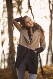 One young girl Caucaisan candid portrait,. Looking at camera. backlit sunny sunset, forest autumn winter clothes Stock Photography