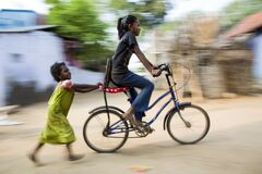 Free One Young Girl Enjoy Riding Bicycle, Another Little Girl Holding And Following Her Stock Photo - 175846470