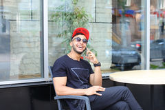 One young handsome arabian guy uses and talks on phone, smiles a Stock Image